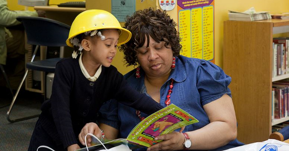 A preschooler reads to her grandmother during a Family Financial Fair at the Weequahic Branch.