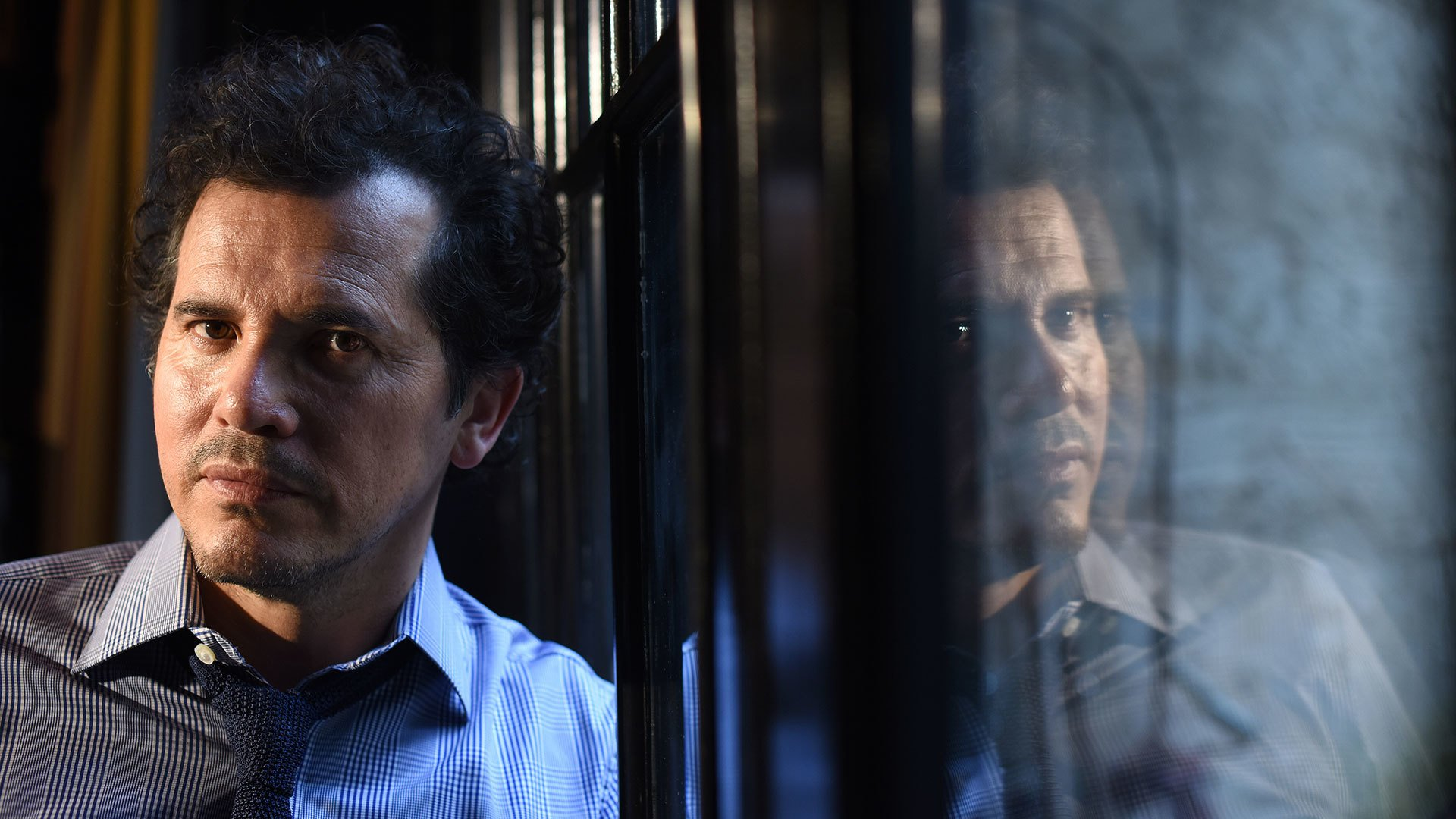 John Leguizamo at window