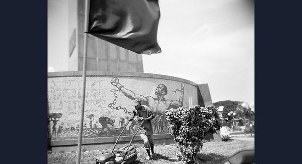 This monument to Angola's first president Agostinho Neto was erected in 2001-2 as a gift from North Korea. This photograph contrasts the heroic figure symbolizing freedom from colonialism with the everyday heroism of a man pushing a heavy lawnmower.