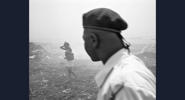 WOMAN AND HER BABY, ROQUE SANTEIRO MARKET: Conflict between Luanda's population and its governing elites forms an undercurrent to this photograph of a young woman carrying a baby across litter-strewn ground, observed by a man wearing a military beret.