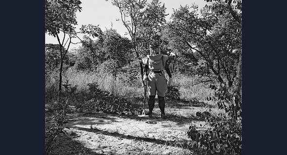 "DEMINER NEAR CUVELAI: The metal detector in the ""deminer's"" hand casts a sinister circular shadow on the ground at his feet, hinting at the landmines that may be concealed all around him."