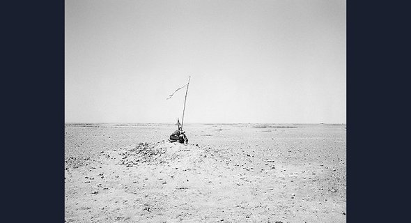 An assemblage of objects perches on a stony outcrop, surrounded by desert. The long pole protruding from the pile is topped with a ragged banner, announcing the presence of this unusual memorial, but giving little away about its exact significance